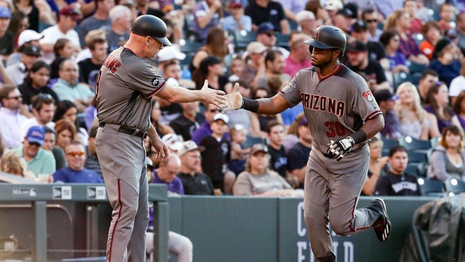 Arizona Diamondbacks center fielder Socrates Brito (30) celebrates with third base coach Matt Williams (9) after hitting a two run home run in the third inning against the Colorado Rockies at Coors Field.