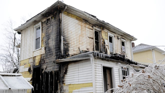 A house in the 600 block of Garfield Avenue stands frozen after a fire there was put out Sunday night.