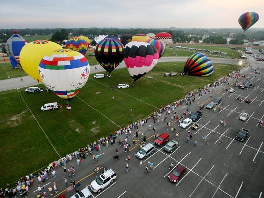Hot air balloons lift off from the Indiana State Fairgrounds at dawn at the 152nd Indiana State Fair.