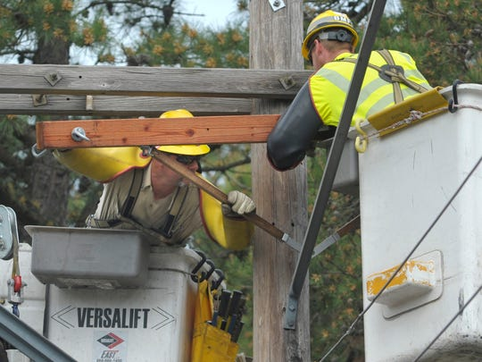 Atlantic City Electric linemen Jim Donovan (left) and Keith Santora replace equipment on a utility pole.