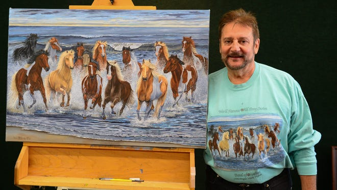 Chincoteague artist Kevin McBride stands next to his 35th Chincoteague Pony Penning poster painting, 'Band of Brothers,' a tribute to 14 stallions, the Chincoteague Volunteer Fire Company and the Saltwater Cowboys, on Thursday, July 11, 2018.