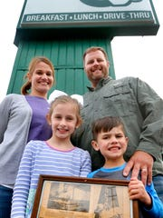 Donut Country owners Kristy and Bo Davis stand in front of the marquee with children Bennett, 5, and Hadley, 8, on Thursday, April 5, 2018. The children are holding a newspaper article showing Kristy with her sister and parents, Rick and Carol Egles, who bought the business in 1986.