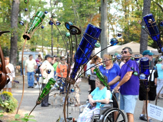 Visitors walk by bottle flower sculpturs by Sandra Webberking of Sandra Webberking Originals in Springfield, Pa., during the annual Festival of Fine Craft at the Wheaton Arts and Cultural Center in Millville.