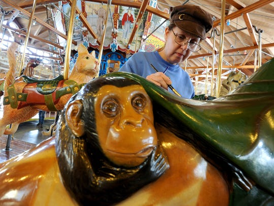 Theresa Rollison of Marion touches up paint on the carrousel at the Richland Carrousel Park on Friday.