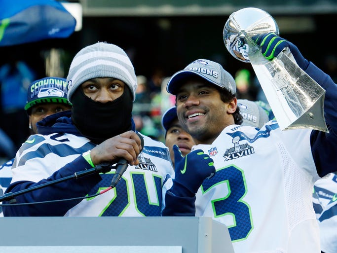 Seahawks QB Russell Wilson (3) and RB Marshawn Lynch show off the Lombardi Trophy at CenturyLink Field on Wednesday.