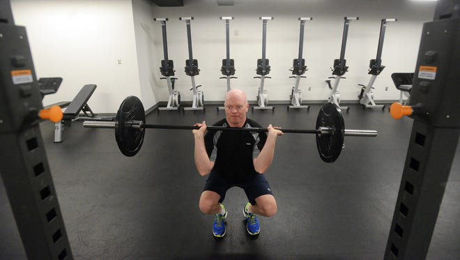 Shon Krull does squats with a weighed bar Tuesday during a group fitness class at DocuTap, April 7, 2015.