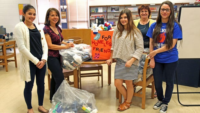 (From left) Michele Berrios, Millville Senior High School Principal Kathleen Procopio, Katie Helig, media specialist teacher Kathleen Galarza and Emma Sedeyn are pictured with socks that were collected at the school as part of the Family Strengthening Network's sock drive to benefit homeless people in Cumberland County.