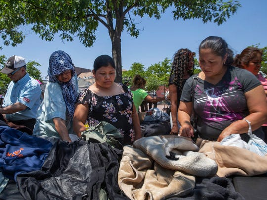 Some of the poor of Lakewood sort through clothing from the Howell homeless camp that they are giving away as they prepare to move out.