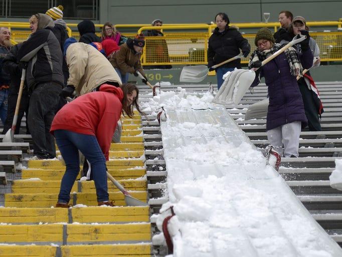 Volunteers shovel snow onto a slide Monday, Dec. 18,