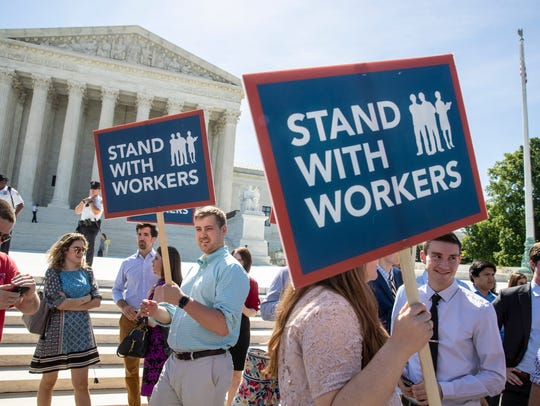 In this June 25, 2018 photo, people gather at the U.S. Supreme Court in Washington awaiting a decision in an Illinois union dues case, Janus vs. AFSCME.