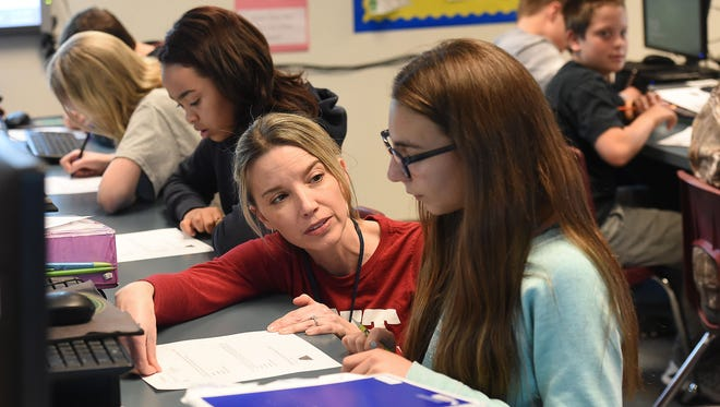Math teacher Carrie Koch works with student Cecilia Lemas at Wellington Middle School on Tuesday, March 22, 2016.