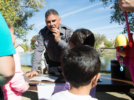 Sgt. Chris Ortega, with the New Mexico Department of Game and Fish, explains to the kids gathered around his booth about the types of fish they can fish for in New Mexico, Saturday March 25, 2017, at the Kids Fishing Clinic at New Mexico State University's Duck Pond.