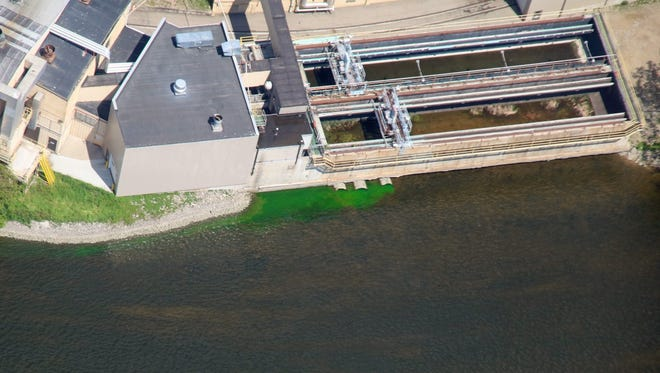 An aerial photo shows green dye flowing from the Menasha lock canal into the Fox River through pipes underneath Sonoco U.S. Paper Mills in Menasha.