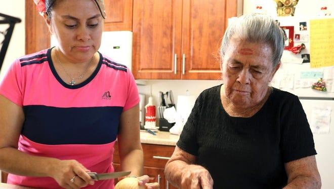 Arminda Perez-Castillo (right) prepares dinner with her daughter Luz Romero.