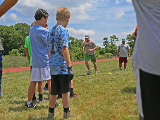 Green Bay Packers tight end Justin Perillo, a Tatnall School graduate, shows how to run the next drill with  kids in a football camp at Tatnall on Thursday.