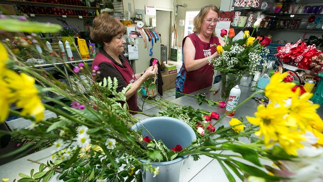 Flowerama owners Donna Watson, left, and daughter Danette Melton work on a bouquet of flowers together on Wednesday at the store.