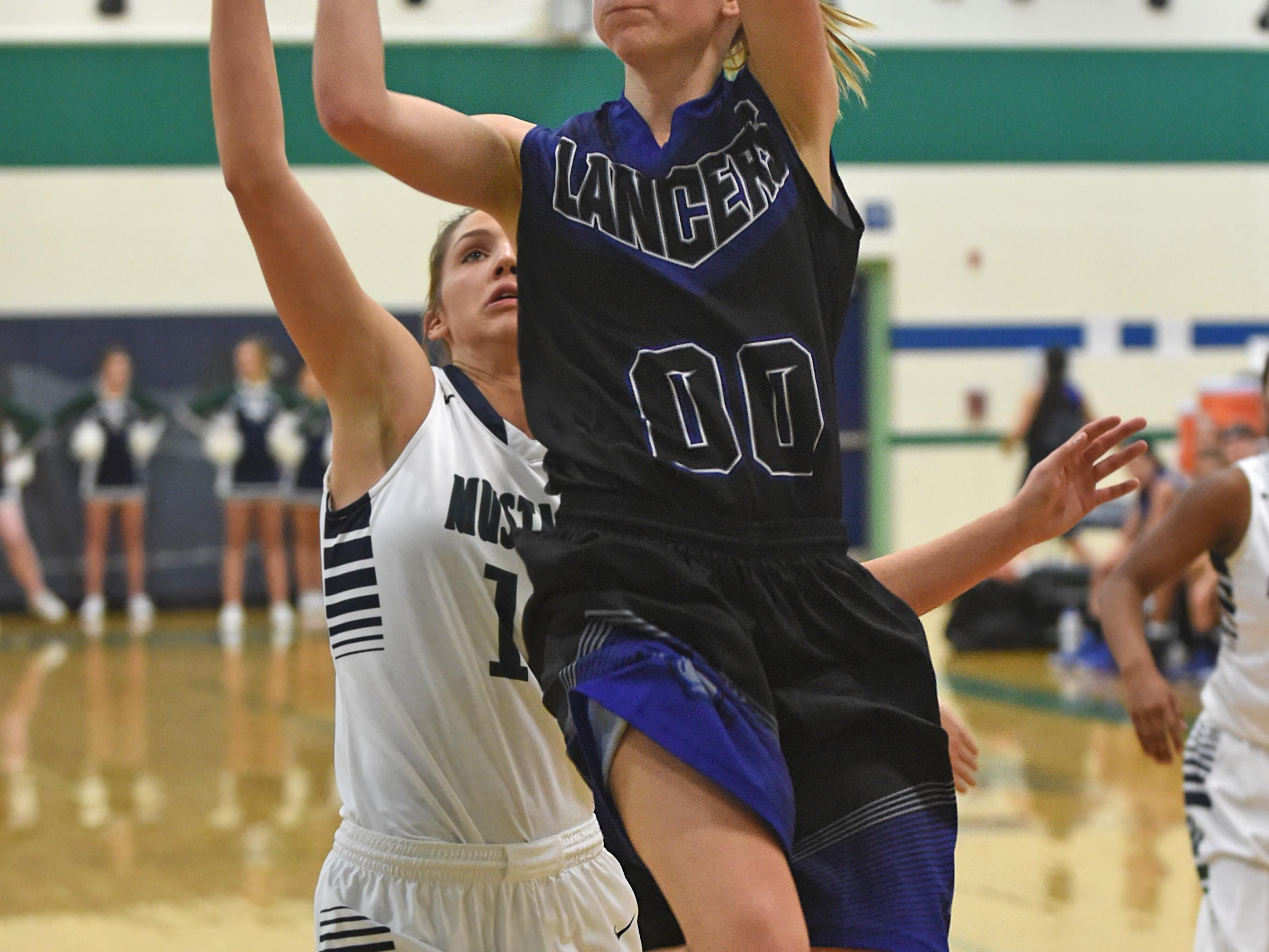 McQueen sophomore Izzy Warren goes up to score with Damonte's Morgan Waller covering her in Tuesday's game at Damonte Ranch High School.