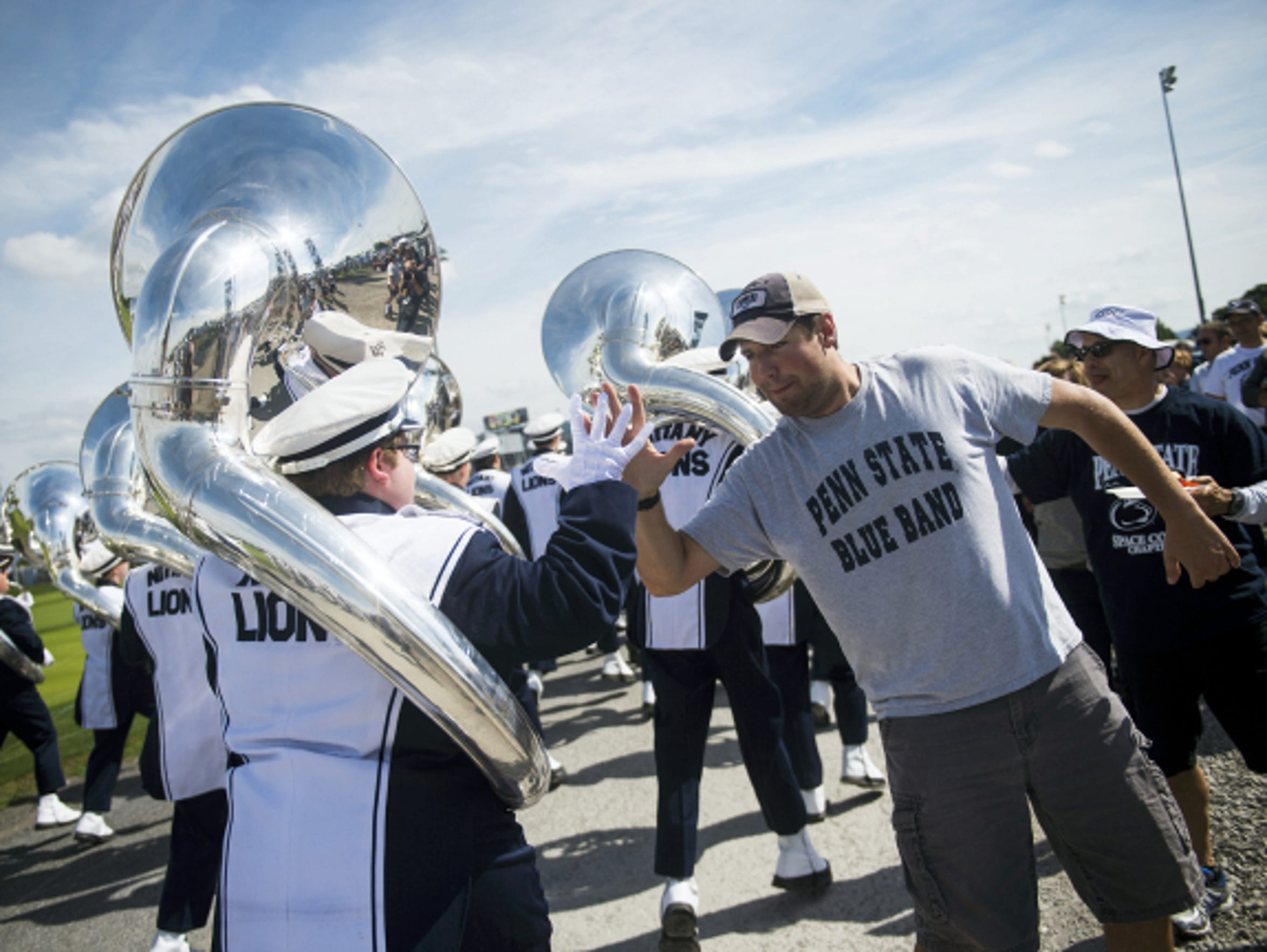 Fans high-five band members as the Penn State Blue