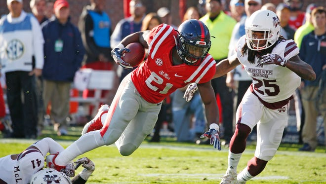 Ole Miss running back Akeem Judd is stopped by a shoestring tackle by Mississippi State defensive back Mark McLaurin (41) with the help of Lashard Durr (25) in the first half.