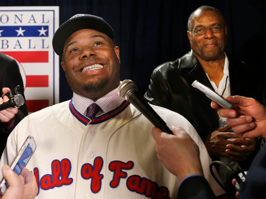 Newly-elected Baseball Hall of Fame member Ken Griffey Jr. conducts interviews with his father, Hall of Famer Ken Griffey Sr. listening in after a press conference announcing that he and Mike Piazza  were elected to baseball's Hall of Fame, Thursday, Jan. 7, 2016, in New York. Both men will be inducted into the Hall of Fame this summer. (AP Photo/Kathy Willens)