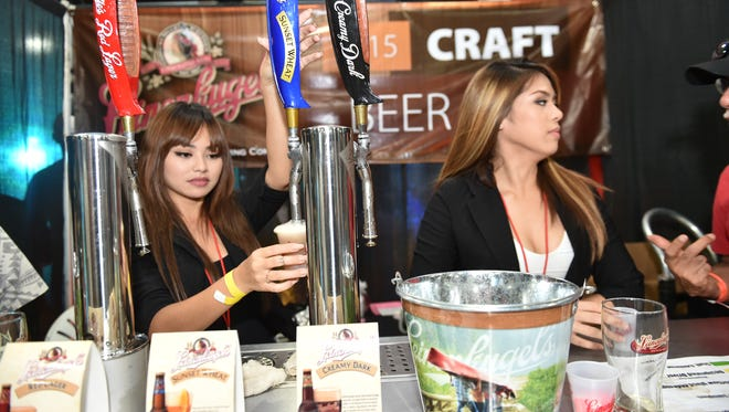 Jerlaine Quidachay pours a sample of Leinie's Sunset Wheat at the Craft Beer Festival at Guam Greyhound Park on Sept. 26.
