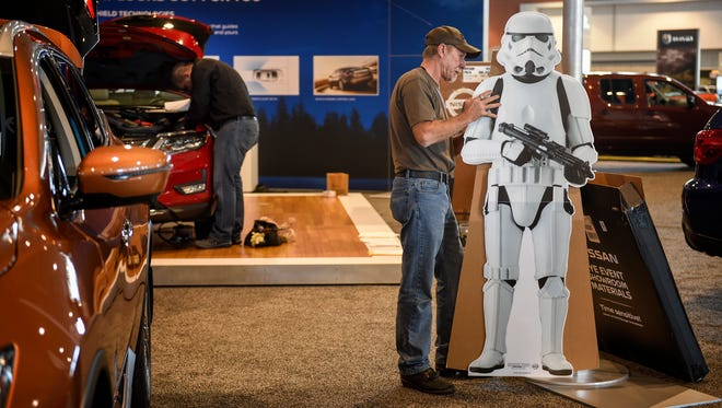 """Cled Caraker sets up a cut-out of a """"Star Wars"""" character for the Nissan booth at the Nashville International Auto Show on Thursday, Nov. 17, 2016, at Music City Center. The show runs through Sunday."""
