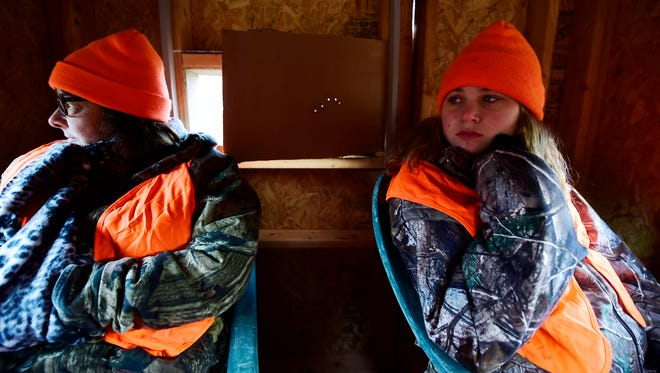 Cheryl Howell, left, and her granddaughter Taylor Howell, 15, sit in a two-person blind waiting for deer on Cheryl's property in Fawn Township. Taylor started tagging along with her father as he hunted when she was five or six years old. This is the last year she'll require a licensed adult to be with her as she hunts.