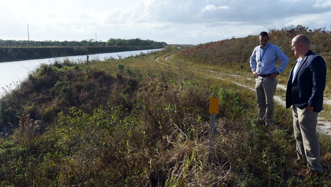 Port St. Lucie utility director Jesus Merejo (left) and mayor Greg Oravec stand along the C-23 Canal on Tuesday, Dec. 20, 2016, that runs adjacent to newly added land to the McCarty Ranch Preserve. City officials are looking to build reservoirs on the land that will remove polluted water from the canal that would normally run into the St. Lucie River and Indian River Lagoon.
