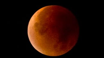 The Earth's shadow obscures the view of a so-called supermoon during a total lunar eclipse over Antwerp, Belgium, Monday, Sept. 28, 2015. Supermoon, or perigee moon, is the name given when the full or new moon comes closest to the Earth making it appear bigger. (AP Photo/Virginia Mayo)