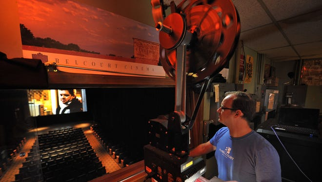 Head projectionist Kirk Futrell adjusts the focus on a 35mm projector at the Belcourt Theatre, which screens both film and digital motion pictures.