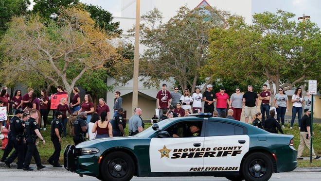 In this Feb. 28 photo, a police car drives by Marjory Stoneman Douglas High School in Parkland, Florida, as students returned to class for the first time since a former student opened fire there with an assault weapon.