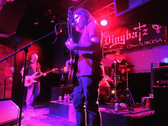 SideSlam performing at Dingbatz in Clifton. The band's members include Carter Olcott on lead guitar and vocals, Joel Stearns on bass guitar and Marc Grossman on drums.