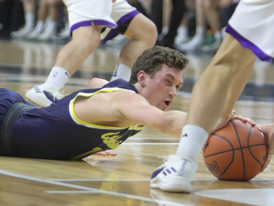 Clarkston's Foster Loyer dives for the loose ball against