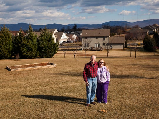 """Jim and Debbie Thompson stand in their yard which overlooks the Blue Ridge Mountains in Waynesboro on Jan. 18. """"There's nothing like waking up and seeing this in the morning,"""" Jim said, citing their view as one of the primary reasons for the couple's recent move to the area."""