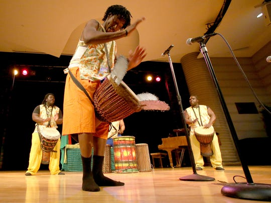 Osier Carbin of Detroit gets near the front of the stage playing an African drum during the start of the Kwanzaa celebration inside the Charles H. Wright Museum of African American History in Detroit on Saturday, Dec. 26, 2015.