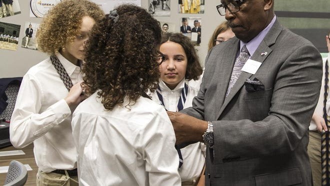 Larry Robbins, deputy superintendent of operations for USD 501, fixes a student's tie during a jacketing ceremony for the 2019 College Prep Academy class at the Topeka Center for Advanced Learning and Careers.