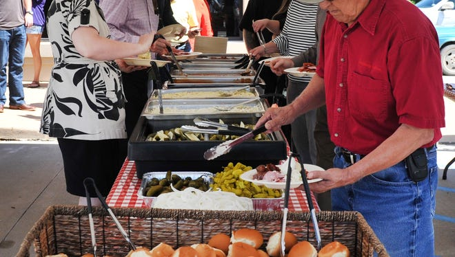 Guests lined up for barbecue Tuesday afternoon for the 19th annual Guarantee Title customer appreciation luncheon held in the business's parking lot located on Midwestern Parkway. Guaranteed Title president and CEO Kolter Lukert said, the event caters between 350 to 400 people every year. This year's event had live music by the Lone Star Troubadours.