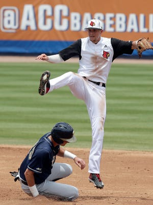 Pittsburgh's Nick Banman is out at second base as Louisville infielder Devin Mann jumps after making a throw to first base during the second inning of an Atlantic Coast Conference NCAA college baseball tournament semifinal game in Durham, N.C., Saturday, May 26, 2018. (AP Photo/Gerry Broome)