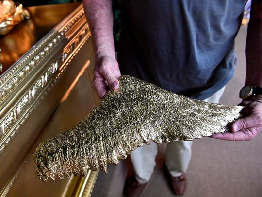 Graham Gutting holds one of the angel wings May 3 for the Ark of the Covenant replica he made for the Discovery Center.