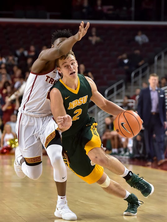 North Dakota State guard Paul Miller (2) gets by Southern California guard Jonah Mathews, left, during the first half of an NCAA college basketball game, Monday, Nov. 13, 2017, in Los Angeles. (AP Photo/Gus Ruelas)