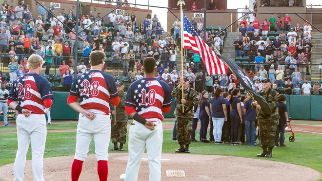 Players salute the flag during the Rawhide's 70th anniversary celebration.