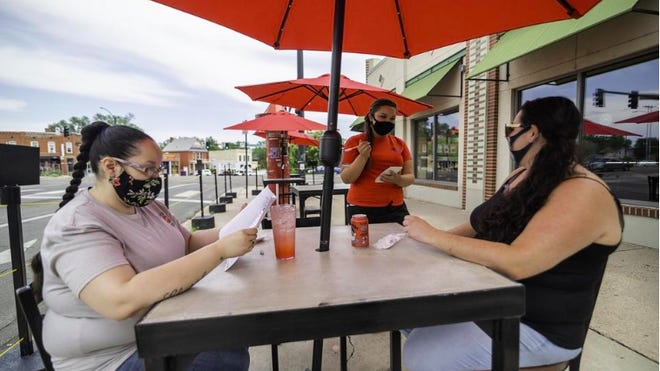 Jazzy Romero, center, takes down orders from Liz Ashton, right, and Christina Garcia, left, in July at the outside dining area of Colorado Taproom, 106 Colorado Ave.