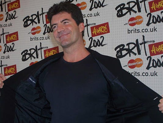 Presenter at the annual Brit awards Simon Cowell shows off his jacket to the photographers backstage at the awards in London Wednesday, Feb. 20, 2002. Cowell was one of the judges in the recent 'Pop Idol' series on television. (AP Photo/Alastair Grant,/Pool)