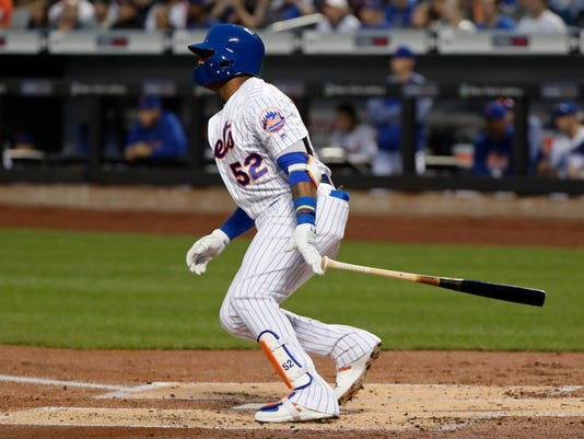 New York Mets' Yoenis Cespedes (52) hits an RBI-single during the first inning of a baseball game against the Milwaukee Brewers, Friday, April 13, 2018, in New York. (AP Photo/Frank Franklin II)