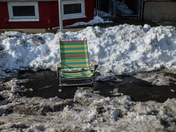A beach chair is left in a shoveled parking space on a public street in the South Boston neighborhood. Every winter, following a snow storm, the tradition of marking the parking space that one has shoveled with a disposable object continues in the Boston neighborhoods.