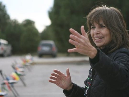 Rachel Beaver waves to vans carrying students to House of Faith Christmas parties in this Standard-Times file photo. Beaver is a co-founder of House of Faith Ministries and retired 2016.
