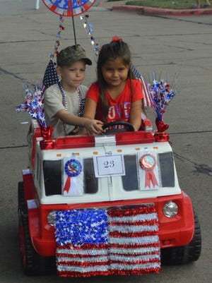 A couple of Fourth of July parade participants were finished with their miniature motorized fire truck as they continue to sputter around on Bluff Street in front of the Kell House Tuesday morning.