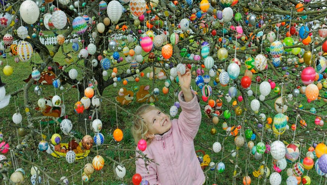 Jette Kuehlwei stands among around 9,500  Easter eggs in the garden of Christa and Volker Kraft in Saalfeld, Germany, in 2010. The Kraft family have decorated their tree at Easter time for decades.