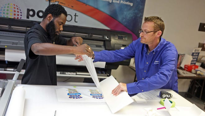 Keith Roberts, 22, a former foster child, and Gary Nolan, a production supervisor, work together at popdot signs and graphics Wednesday. Roberts was cleaning the printer heads as part of his job.