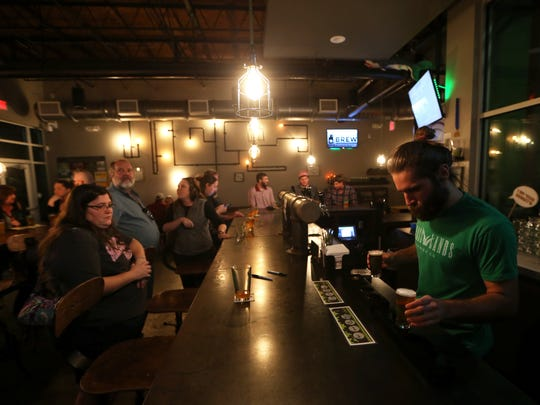 Bartender Andrew Pitts sets out a tasting flight of in-house brews at Grasslands Brewery.